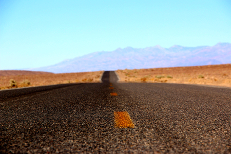 Road in the Death Valley National Park with colorful sky background, California.