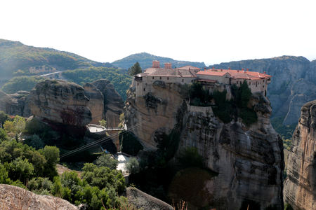 Meteora monasteries. Beautiful day time view on the Holy Monastery of Varlaam placed on the edge of high rock Roussanou Monastery on background. Kastraki Greece