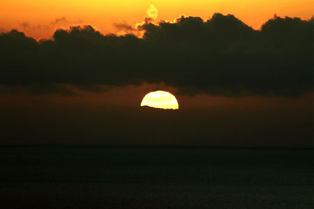 The bright sun between clouds during sunset in Oia, Santorini. Stock Photo