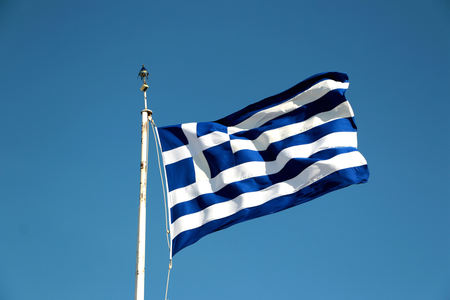 national flag of Greece against blue sky background. Foto de archivo