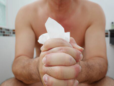 man in toilet has problems with the digestive and holding painful tissue