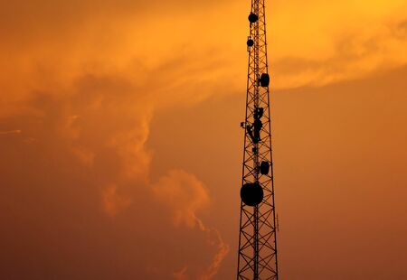 the telacommunication pole with sunset sky background. the silhouette electric workers working on high ground with safety uniform.