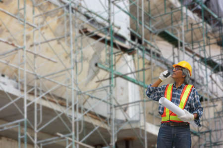 A engineer using radio talking to team work to control the project  in construction site