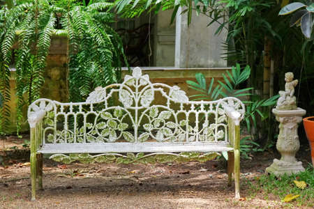 vintage iron bench in white color in garden