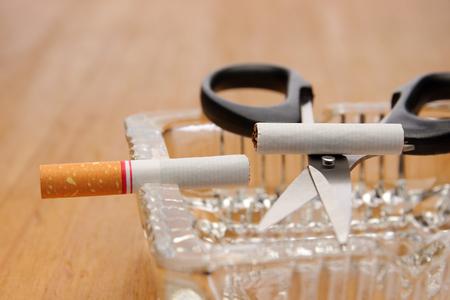 pernicious: scissors cut a cigarette on ashtray, stop smoking concept