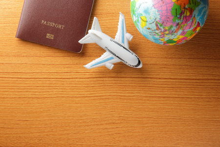 plane table: toy plane with passport and world globe on wood table