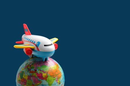 colorful plastic toy plane on world globe in blue background