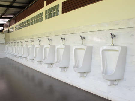 row of urinals men public toilet in petrol station