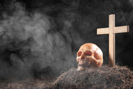 skull and cross on graveyard in dust and smoke , air pollution concept