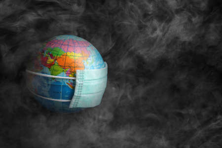 world globe with face mask in smoke , environment concept