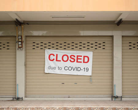 "shophouse sign with wording "" closed due to covid 19 "" hanging on the door"