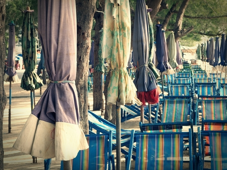 vocation: Line of colorful umbrellars and beach chairs for tourism relax in vocation at Cha-Am beach, Thailand