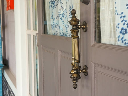 door handle: Metal door handle on wooden door