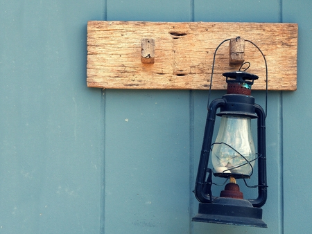 scintillating: Burning kerosene lamp hang on the wooden wall. Home decoration by old lamp in vinage style. Stock Photo