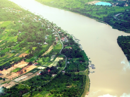 arial view: Arial view over small village near the river in Thailand. City skyline background.