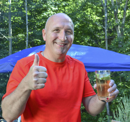 thumbup: Man in a red tshirt showing a thumbup while holding a drink. Stock Photo