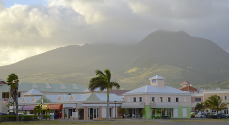 caribbeans: colour picture of a small colourful Caribbeans mall at the foot of a huge volcanic mountain.