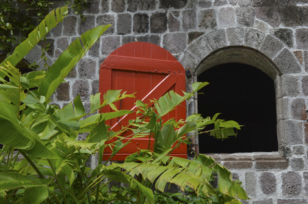 caribbeans: Open wooden red shutter on an old stone house