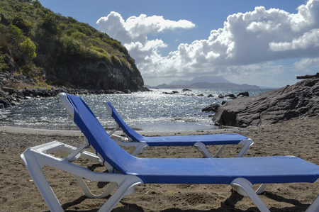 caribbeans: two empty blue chairs on a sandy beach overlooking a secluded lagoon in the caribbeans. Stock Photo