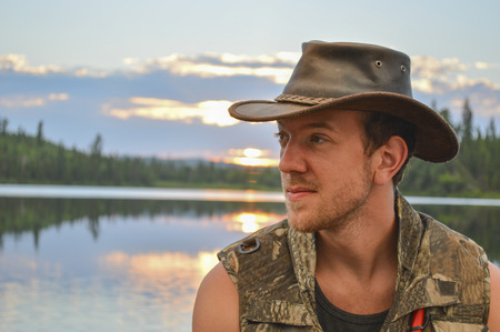 safety vest: Handsome young fisherman on a lake wearing a leather hat and safety vest, waiting  for the sunset