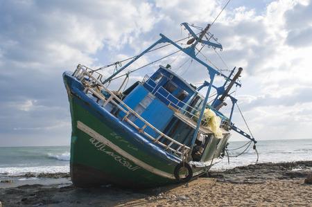 albero: barca abbandonata sugli scogli, ragusa, sicily, italy