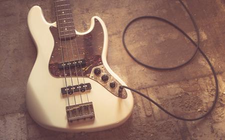 basement: old vintage electric bass guitar on basement floor