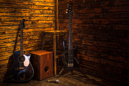 Cajon, bass and acoustic guitar on wooden stage in pub Stockfoto
