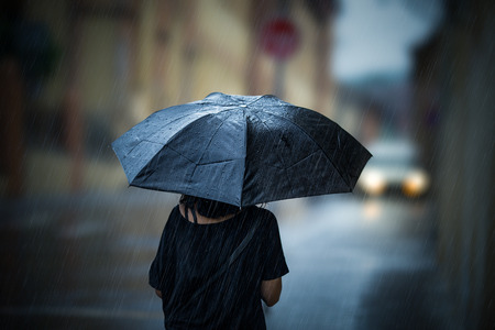 Girl walking with umbrella on rainy day Stock Photo