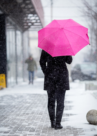 Woman with pink umbrella on snowy day
