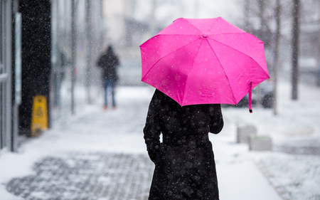 Woman with pink umbrella walking on snowy winter day