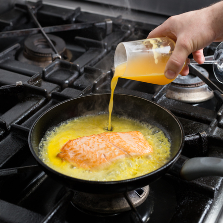 Frying salmon in citrus marinade Stock Photo