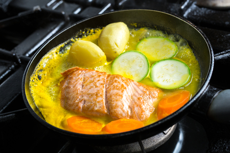 Frying salmon in pan with vegetables in citrus marinade