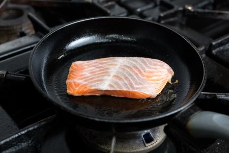 Frying salmon fillet in pan Standard-Bild