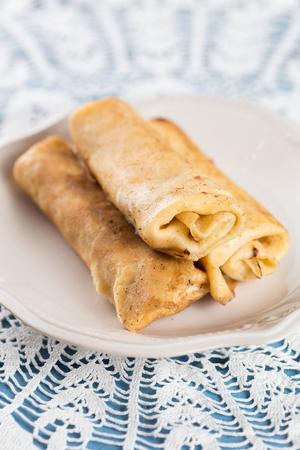 Three homemade rolled pancakes on plate Standard-Bild