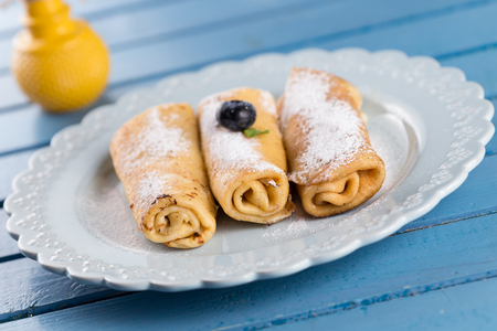 Three homemade rolled pancakes with blueberry Stock Photo