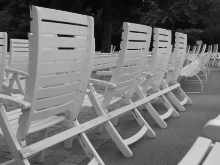 Line of white club carden chairs in park