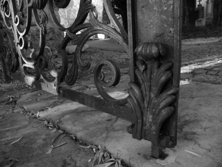 Old rusty metal fence entrance gate from bottom in black and white