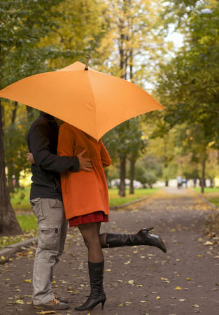 he she: in Love couple standing under an umbrella in the autumn park