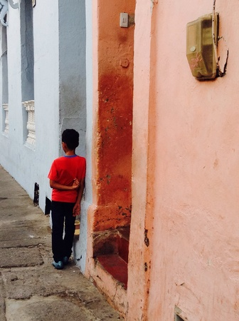architecture: Little boy leaning against his house