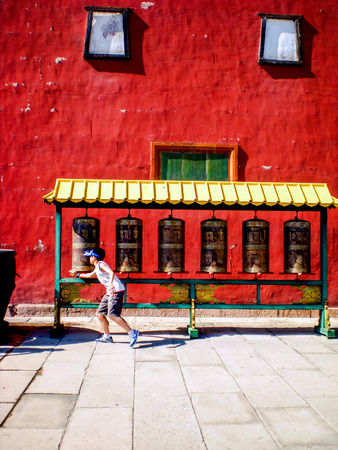 little boy turning the wheel at a buddhist temple ( Putuo Zongcheng)