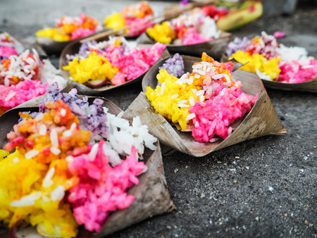 Rows of bright yellow and pink rice offerings in palm leafs on the pavement at Saka new years eve during Nyepi, Nusa lembongan, Bali, Indonesia Stock Photo