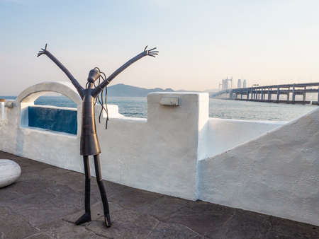 Metal sculpture on the Haeundae promenade promoting the Busan International Film Festival with the Gwangan bridge in the background during sunset, Busan, South Korea