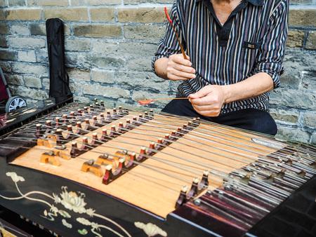 中国の橋の5つのコースで現代の yangqin に竹ハンマーで遊んで老人