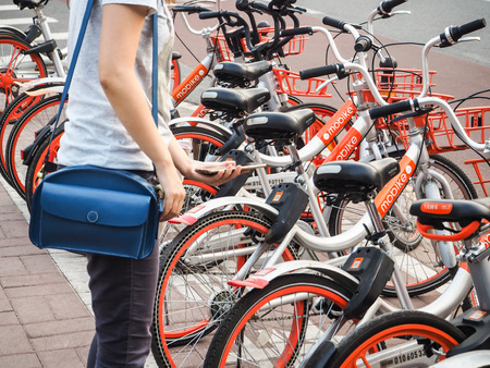Beijing, China - September 2017: Young woman making use of the Mobike bicycle sharing platform by using her smartphone to scan the QR code and unlock the bike Redakční
