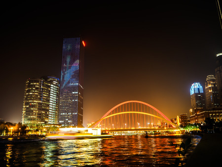 Night view from the promenade on the modern illuminated buildings next to the Hai river