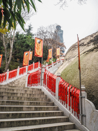Qingdao, China - December 2017: Stairs full with red wishing cards  winding up to the worlds largest statue of Laozi at te Taiqing temple on Laoshan Editorial