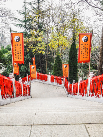Qingdao, China - December 2017: stairs hanging full with red whishing cards and flanked by orange taoist flags at the Taiqing temple on mountain Lao