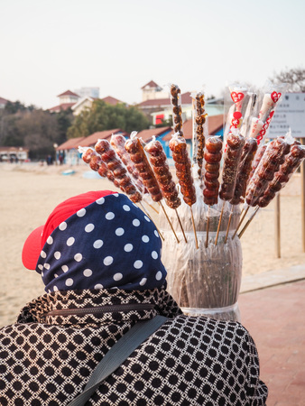 Older lady selling candied fruit on a stick on a beach in Qingdao