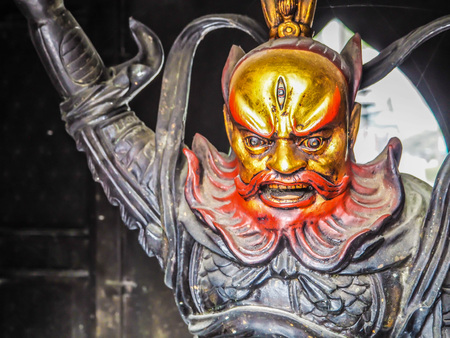 Qingdao, China - December 2017: Close up of a warrior sculpture guarding the entrance of the Taiqing temple at Mt. Laoshan