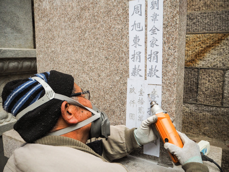 Qingdao, China - December 2017: Older man carving names and donation amount on s stele in Taiqing temple, Laoshan